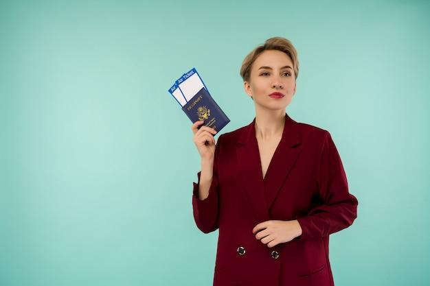 Portret van grappige jonge vrouw met paspoort en instapkaart op blauw