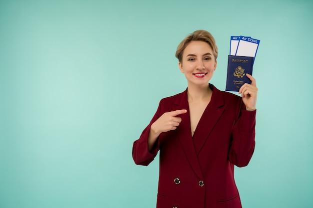Portret van grappige jonge vrouw met paspoort en instapkaart op blauwe achtergrond. grenzen openen. begin van vliegreizen na een pandemie.