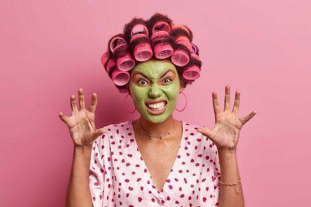 Portret van grappige jonge vrouwelijke model klemt tanden en werpt handpalmen, toont poten, gekleed in zijden badjas, maakt kapsel met krulspelden, krijgt schoonheidsprocedures, bereidt zich voor op disco party