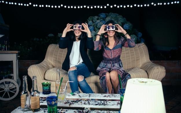 Portret van grappige jonge vrouwen die smartphones over hun gezicht houden en mannelijke ogen op het scherm tonen op een buitenfeestje. vriendschap en vieringen concept.