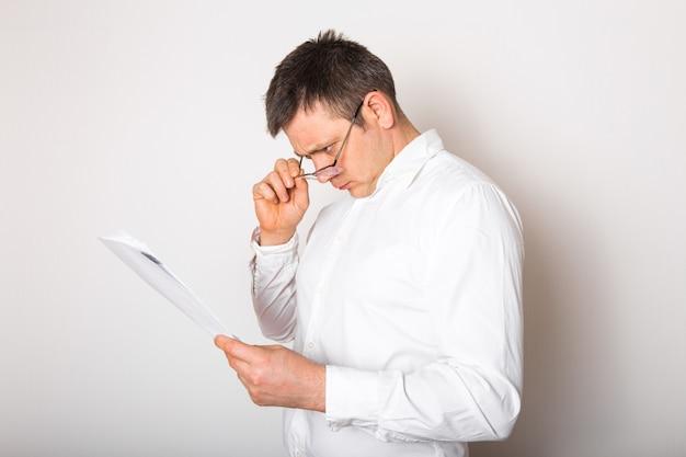 Portret van grappige kaukasische geschokte zakenman verrast met open glazen om financieel verslag, slecht nieuwsconcept te zien