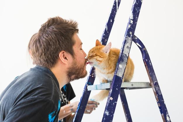 Portret van grappige kerel met kat die opknapbeurt binnen doet