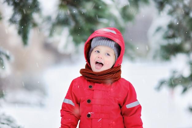 Portret van grappige kleine jongen in rode winterkleren met plezier in sneeuwval. actieve openluchtvrije tijd met kinderen in de winter. jong geitje met warme hoed, handhandschoenen en sjaal