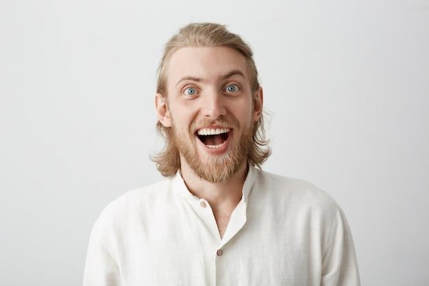 Portret van grappige knappe bebaarde man met blond haar gezichten maken alsof hij gek doet