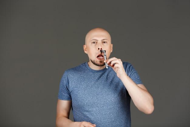 Portret van grappige knappe man in grijs shirt scheren over donkere muur