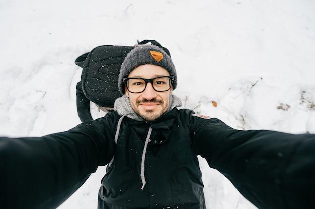 Portret van grappige man in glazen die een selfie in de sneeuw nemen