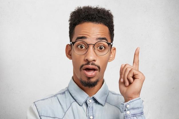 Portret van grappige man met grote ogen, steekt vinger ar herinnert zich om producten te kopen voor het koken van avondmaal