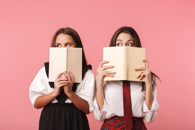 Portret van grappige meisjes die in schooluniform boeken lezen, terwijl status geïsoleerd over rode muur