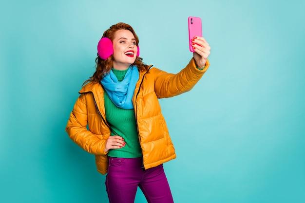 Portret van grappige mooie dame houdt telefoon handen nemen selfies dragen trendy casual oorbeschermers gele overjas sjaal magenta broek trui.
