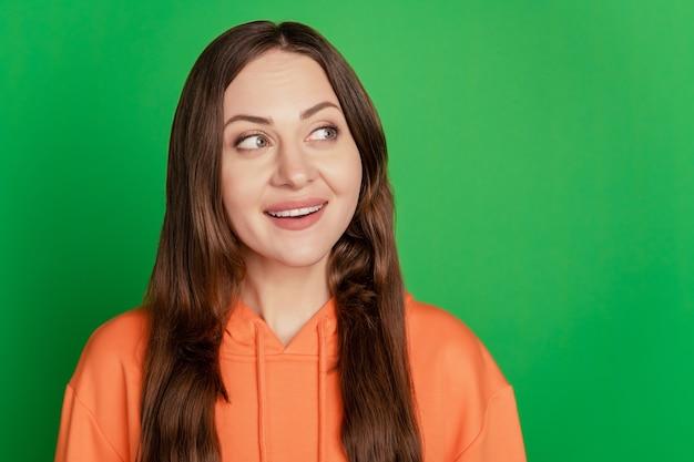 Portret van grappige, mooie geïnteresseerde dame zoekt lege ruimte op groene achtergrond op