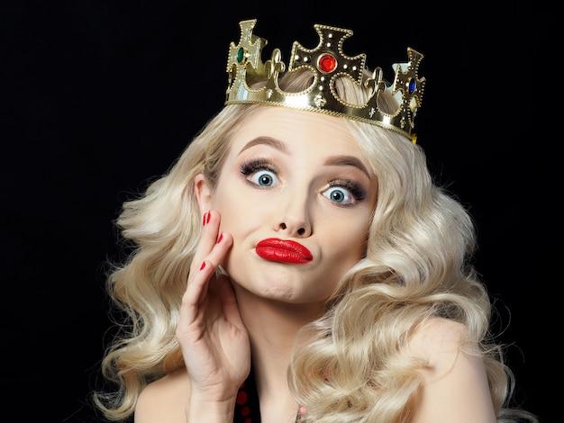 Portret van grappige mooie jonge blondie prinses maakt gezichten