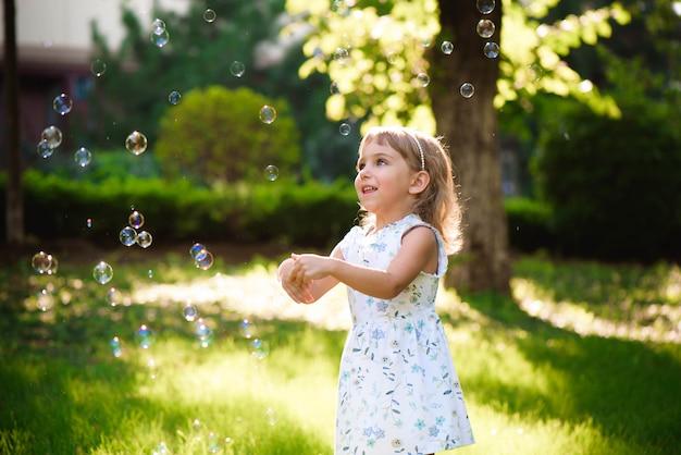 Portret van grappige mooie meisje blazende zeepbels