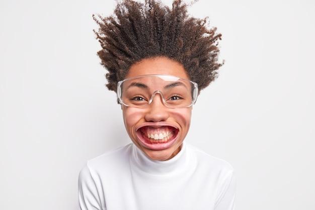 Portret van grappige positieve donkere vrouw glimlacht met tanden heeft grote mouh poses onder luchtdruk heeft haar opstaan gekleed in casual poloneck en grote transparante bril