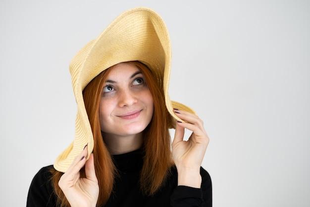 Portret van grappige roodharige vrouw in zak gele strooien hoed.