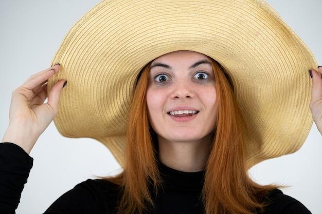 Portret van grappige roodharige vrouw in zak gele strooien hoed