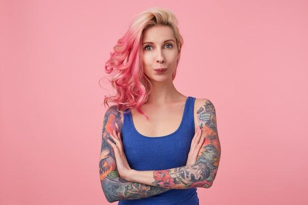 Portret van grappige schattige dame met roze haar en getatoeëerde handen, permanent en kijkend, gekleed in een blauw shirt. mensen en emotie concept.