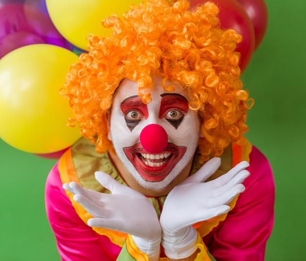 Portret van grappige speelse clown in oranje pruik met ballonnen.