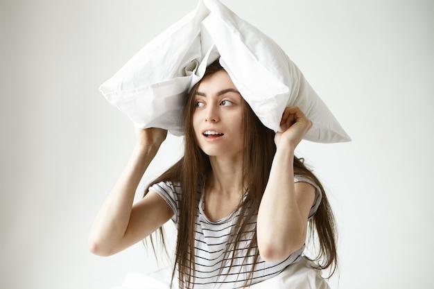 Portret van grappige speelse mooie jonge 20-jarige vrouw met lang los donker haar gestreept t-shirt binnenshuis dragen, zijwaarts op zoek met mysterieuze glimlach, wit kussen boven haar hoofd houden
