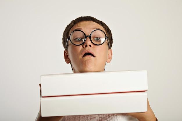 Portret van grappige studente die twee zware grote mappen met educatieve planningsdocumenten voor haar houdt