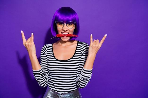 Portret van grappige tiener met pony houden kille peper tonen rocker teken dragen brillen brillen zonnebril gestreepte shirt geïsoleerd over violet paarse achtergrond