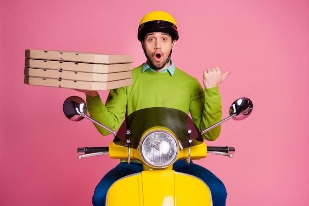 Portret van grappige verbaasde man rijden bromfiets met pizza wijzend opzij