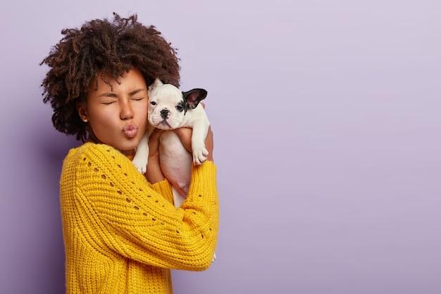 Portret van grappige vrouw brengt vrije tijd door met haar geliefde bulldog-puppy