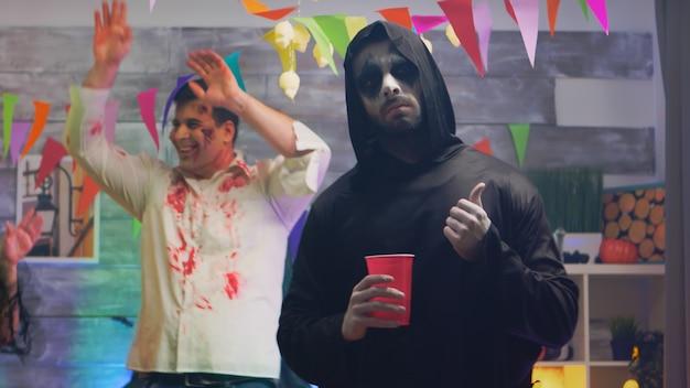 Portret van griezelige magere hein met een glas bier op een halloween-feest. vrienden binden.