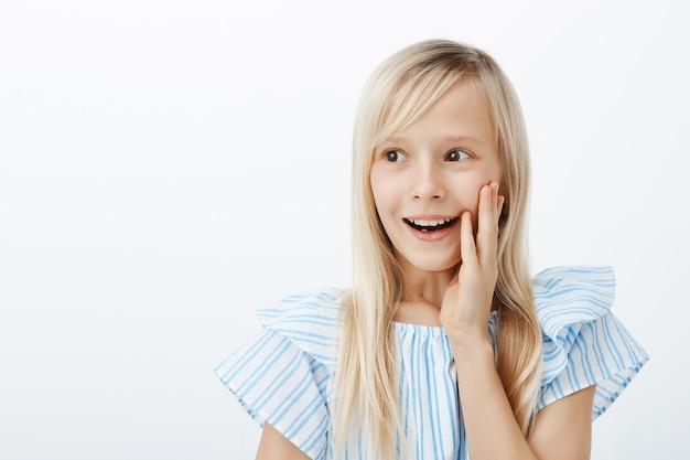 Portret van grijnzend gelukkig klein kaukasisch meisje met lang blond haar, opzij kijkend met pure vrolijke glimlach, hand op wang vast te houden