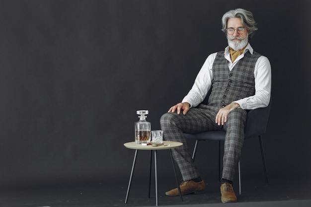 Portret van grijnzende ouderwetse man close-up. gentelman zittend op een stoel. grootvader met een glas whisky.