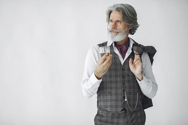 Portret van grijnzende ouderwetse man close-up. grootvader met een glas whisky.