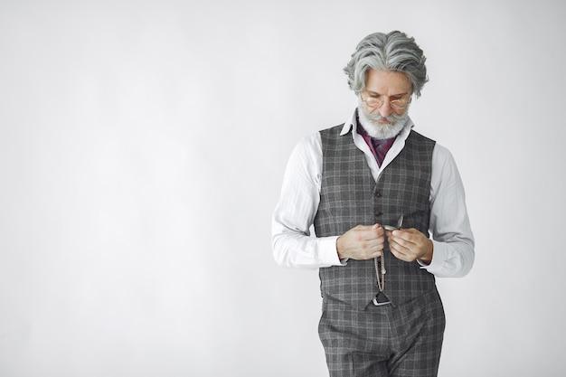Portret van grijnzende ouderwetse man close-up. grootvader met een klok.