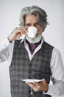 Portret van grijnzende ouderwetse man close-up. grootvader met een mok thee.