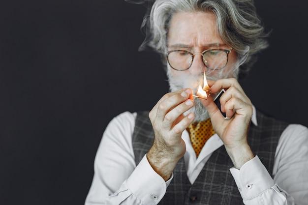Portret van grijnzende ouderwetse man close-up. grootvader met een sigaar.