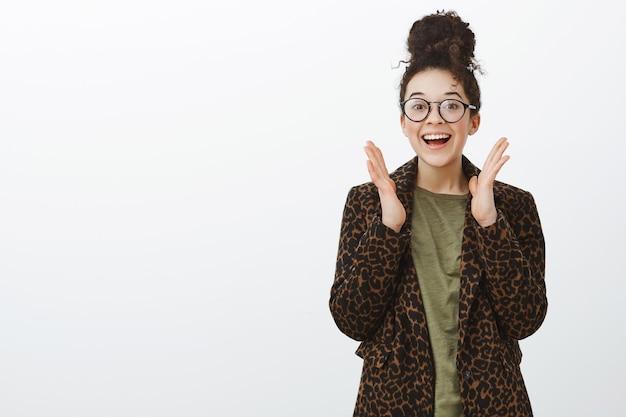 Portret van grijnzende vrolijke vrouw in trendy luipaardjas en zwarte bril, breed glimlachend en handpalmen schudden in de buurt van hoofd, geweldig nieuws horen of juichen voor vriend