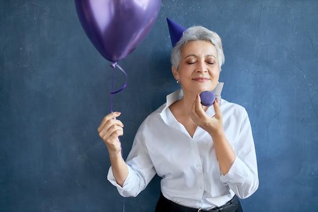 Portret van grijsharige grootmoeder in stijlvol wit overhemd viert verjaardag, ogen sluiten met plezier