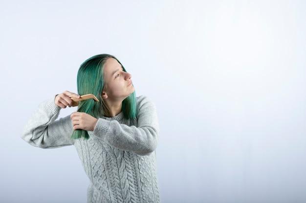 Portret van groenharige meisje dat haar haar op grijs kamt.