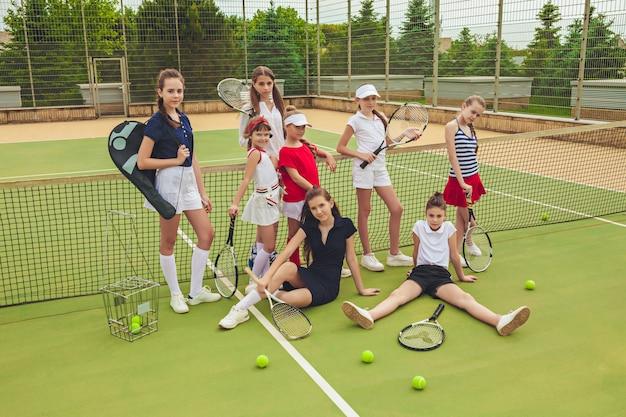 Portret van groep meisjes als tennisspelers die tennisracket houden
