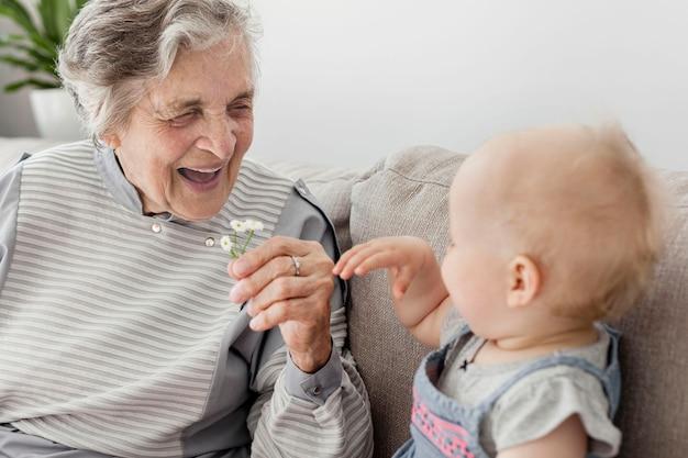 Portret van grootmoeder gelukkig yo spel met baby