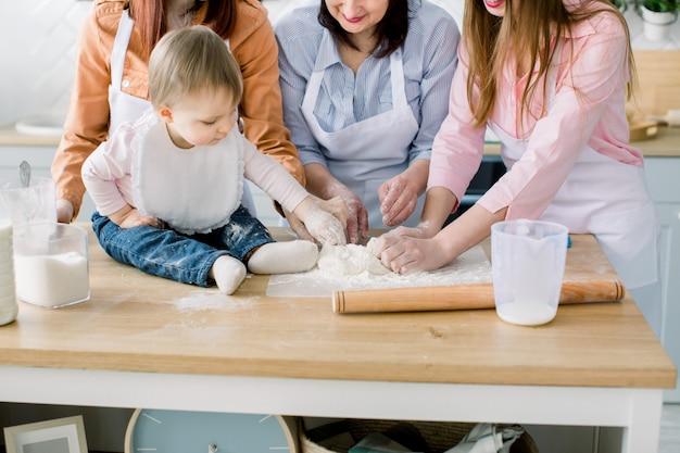 Portret van grootmoeder met haar dochters en kleindochter samen maken diner in de keuken. moederdag concept.
