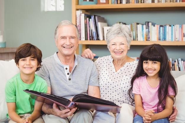 Portret van grootouders die album tonen aan kleinkinderen