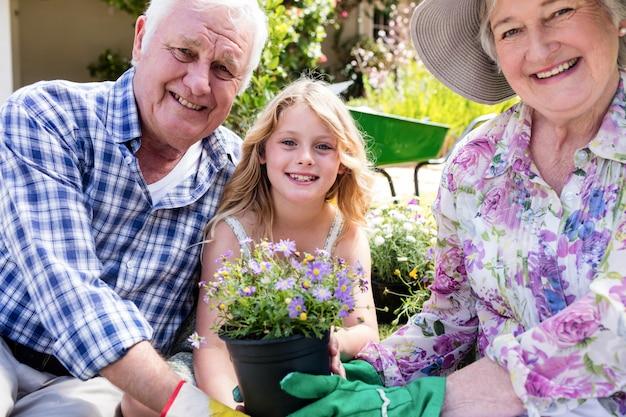 Portret van grootouders en kleindochter die bloempot houden