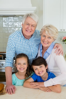 Portret van grootouders en kleinkinderen die zich bij keuken bevinden