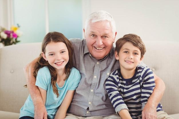 Portret van grootvader en kleinkinderen die samen op bank in woonkamer zitten