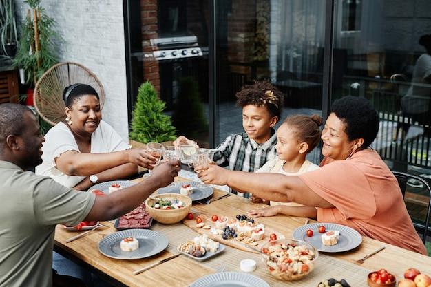 Portret van grote afro-amerikaanse familie rammelende glazen terwijl ze samen genieten van een diner in de buitenlucht en ...