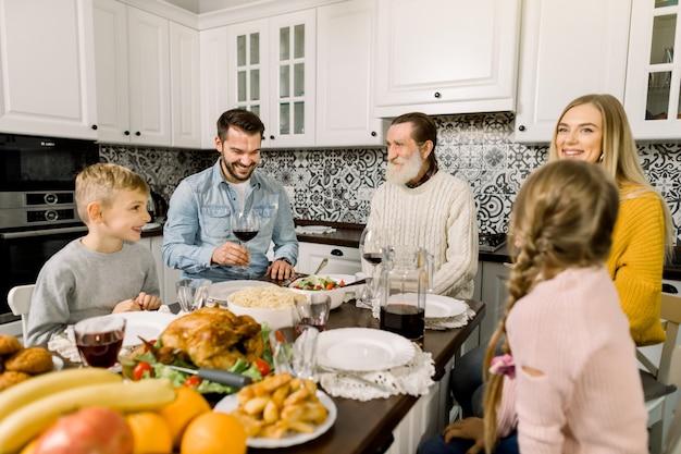 Portret van grote familie aan tafel zitten en kijken naar elkaar, praten en lachen. thanksgiving diner concept