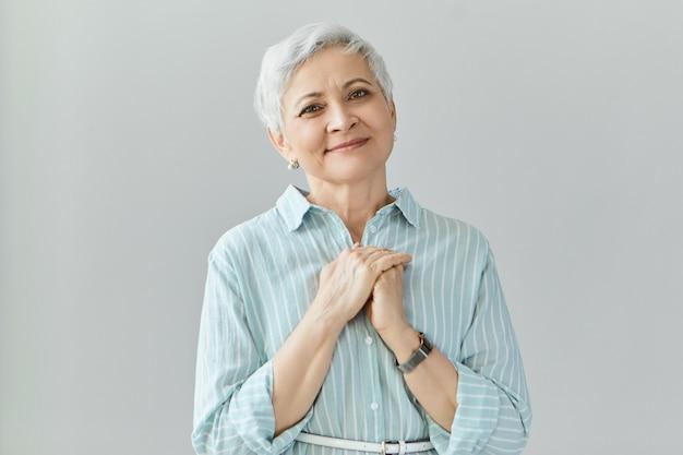 Portret van gulle, vriendelijke volwassen senior vrouw in stijlvol overhemd, hand in hand op haar borst geklemd, dankbaar voor een geweldig cadeau op haar verjaardag. bejaarde vrouw waardering uiten