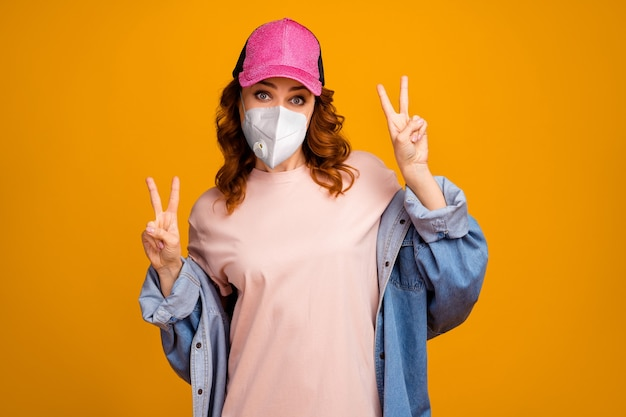 Portret van haar, aantrekkelijk, funky, gezond, golvend meisje met een veiligheids n95-ademhalingsmasker met dubbel v-teken mers cov preventie geïsoleerd helder levendig glans levendige gele kleur achtergrond