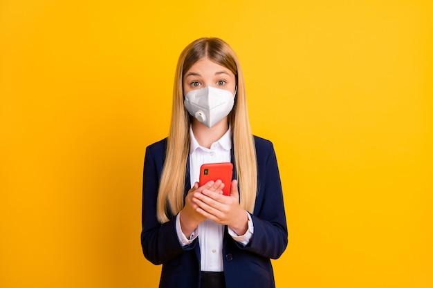 Portret van haar aantrekkelijke zieke zieke ongezonde schoolkind met veiligheidsmasker n95 met apparaat app 5g mers cov thuisblijven zelfisolatie geïsoleerd helder levendig glans levendige gele kleur achtergrond