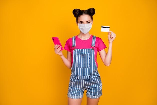 Portret van haar dat ze aardig meisje in de hand houdt met behulp van een plastic kaart van de celbank met een veiligheidsmasker koop een levensverzekering geïsoleerd helder levendig glans levendige gele kleur achtergrond