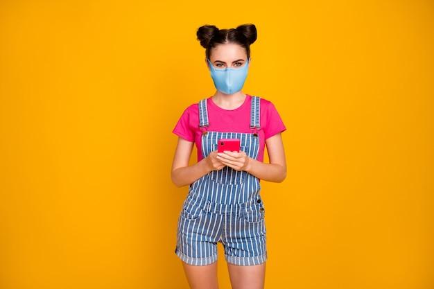 Portret van haar, mooi, aantrekkelijk, gezond meisje met apparaatgadget-app 5g die veiligheid herbruikbaar textielmasker draagt, besmettingspreventie geïsoleerd helder levendig glans levendige gele kleur achtergrond